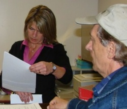 Meg Willamson of the city of Paso Robles accepts box of water rate petitions from John Borst, right, of water fee opponent CCPR.