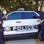 This is a neighborhood policing publicity photo on the city's website -- of officers with parked vehicle on the Murray median, which is unlawful.