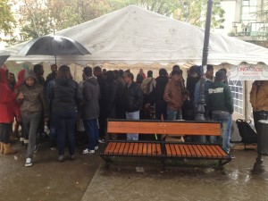 Refugees huddle under a tent on a rainy day in Belgrade