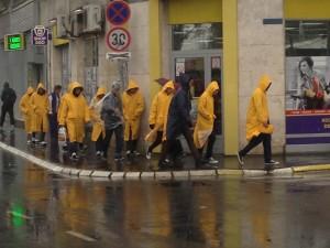 Refugees walk through the rain in Belgrade
