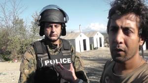 Macedonian border policeman next to an Iranian refugee