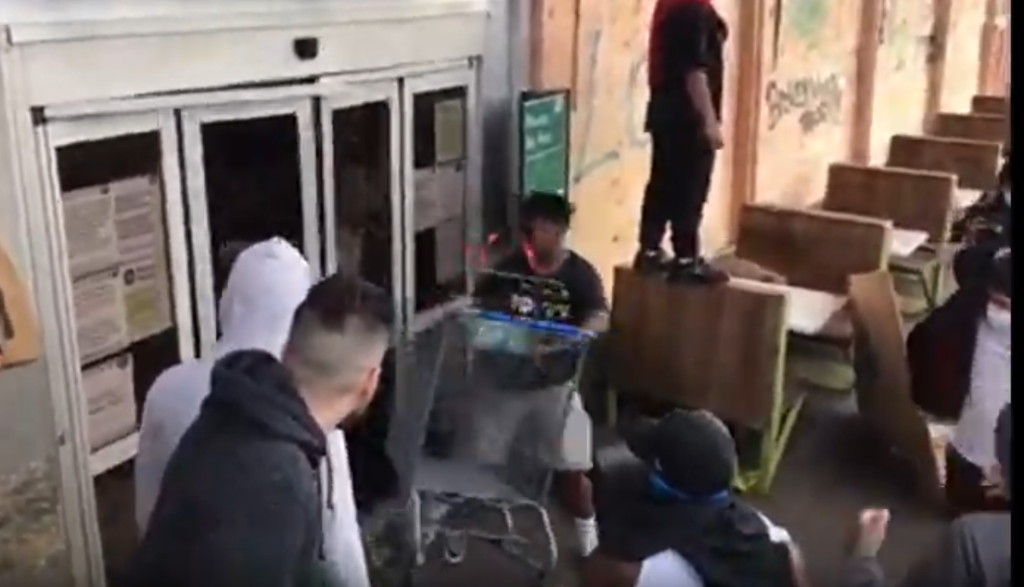 A man breaking the door open of a Whole Foods in Los Angeles. Dozens of looters then stormed the store
